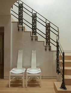 (Laura Ziskin's Home) The custom railing incorporates bronze panels designed by Émile-Jacques Ruhlmann and fabricated by Edgar Brandt for Au Bon Marche in Paris in 1925. The Amsterdam School chairs are circa 1910.