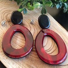 Deze grote rode oorbellen met zwarte knopjes zijn 8 cm lang en 3,7 cm breed. De hanger is donkerrood met zwarte vlekken en een beetje wit erdoor.