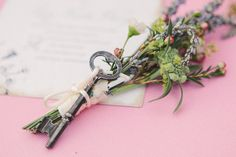 Seeded paper invitations you can plant garnished with the groom's wildflower boutonniere - adorned with a key, of course. All on gorgeous pink chair.