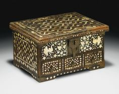 A GOANESE MOTHER-OF-PEARL INLAID WOODEN CHEST  WESTERN INDIA, 16TH CENTURY  Of rectangular form with four wide feet, flat hinged lid, two side handles, large latch and three drawers with internal locking mechanism and metal latches, front with mother-of-pearl inlaid peacocks and stylised floral spray on background of inlaid quatrefoils