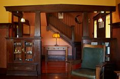 The formal foyer, somewhat unusual for a Craftsman house, showcases stained and shellacked woodwork of Douglas fir. The library table and large Morris chair are Grand Rapids' Lifetime Furniture antiques.