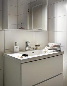 Det lille badet er enkelt innredet i helhvitt for å holde rommet lyst og luftig. Servanten og speilskapet er begge fra Kvik.