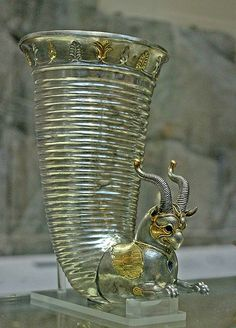 Protome of the gilt silver rhyton. The eye sockets were originally inlaid, as was the necklace with a gem, subsequently detached and missing. Punched dots cover the front of the head and the gilded cheeks. This rhyton was probably used to top up drinking bowls with wine during a banquet, hence the lowermost hole in the chest of the griffin. Possibly found at Altintepe, an ancient Urartian archeological site, Erzincan Province, Turkey.Achaemenid Persian Empire, 5th century BC.