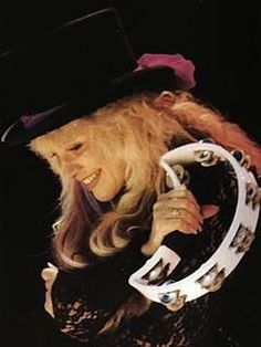 a lovely screen capture of Stevie onstage ~ ☆♥❤♥☆ ~ both arms wrapped around herself, holding a white half-moon tambourine, and smiling ~ love her feathered hat