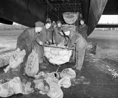 Operation MANNA.  Ground crew loading food supplies into slings for hoisting into the bomb bay of an Avro Lancaster of No. 514 Squadron RAF at Waterbeach, Cambridgeshire.  Between 29 April and 7 May 1945, Lancasters of Bomber Command dropped 6,672 tons of food to the starving populace of a large area in Western Holland still in German hands.