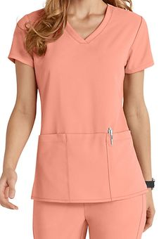 The Grey's Anatomy 3-pocket v-neck top is made of a quality, 4-way stretch material that will last a long time! In addition to the luxurious and soft 4-way stretch fabric, this sophisticated top has three roomy pockets, including a hidden PDA pocket and pen slot to easily carry your favorite accessories throughout the day!  Side slits add ease of movement to this delightful top!   Grey's Anatomy Signature 3 Pocket Criss Cross V-neck Scrub Tops  Criss-cross v-neck  Modern fit  Two patc...