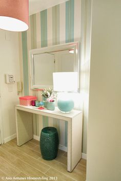 white entryway table // silver wide mirror // turquoise garden stool and lamp // vertical striped walls