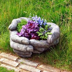 love this hand planter. make a similar planter by filling large plastic gloves with hyertufa mix, shape around a bowl to form, constantly pressing air bubbles out... read more at http://www.bluefoxfarm.com/hypertufa-hands.html and get hypertufa recipe http://en.wikipedia.org/wiki/Hypertufa