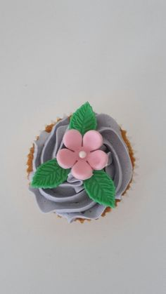 Purple buttercream with a pink flower and green leaves. #cupcake
