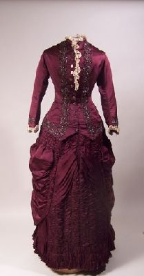 1881 Wedding Dress Culture: English Medium: silk, cotton, glass, metal Front fastening CF to round neck with narrow standing collar, with thirteen buttons with chased ornament. Lower edge lined with silk and cut to point each side of CF. Small pocket below waist on left. Two CB sections open below waist. Long sleeves with frill at wrist. Collar and right front edge and wrists trimmed with cream lace. Front, bottom and wrist edges trimmed with pink glass beads.