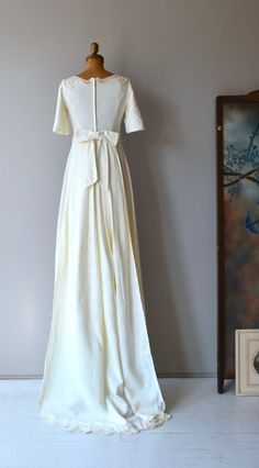 Simply lovely 1960s ivory linen wedding gown with scrolled lace applique shoulders, empire waist with scrolled lace, short slightly fluttery sleeves, slight a-line shape toward the ankles and detachable matching train. --- M E A S U R E M E N T S ---  fits like: xs bust: 32-33 under bust: 26 hip: up to 40 length: 55 brand/maker: Murray Hamburger condition: excellent  ✩ layaway is available for this item  To ensure a good fit, please read the sizing guide: http://www.etsy.com&#x...