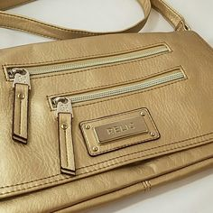 Relic Cross-body Bag in Light Gold. NWOT! This beautiful Relic bag is new without tags. Never been carried and in perfect condition. Interior has many pockets including one zippered pocket. Exterior has several zipper pockets & a built-in wallet on the back as shown. Plenty big enough to carry everything for your night out. Would also make a great travel bag as the pockets are big enough to keep your passport and there's lots of places to hide things. Strap is adjustable. Soft faux leather…