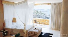 A canopy of Indian mosquito netting hangs over the bed; the wood floor is painted white.