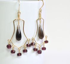 These unique chandelier earrings are as intense as they are exotic. The combination of silky, curvy wire with smokey gray and deep burgundy