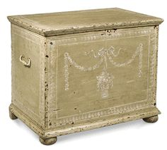"Hand painted and heavily distressed, this crudely made piece is decorated with a contrastingly graceful basket of flowers suspended from ribbons and garlands in a delicate color scheme of grey and white on pale celadon green. A hinged lid, forged handles and bun feet complete this sturdy chest. Gorgeous at the end of a twin bed or in the bathroom filled with rolled towels. (SA)    31"" wide x 21"" deep x 25"" high"