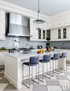 Willy Rizzo stools line the island in the kitchen, which is outfitted with cabinetry by Smallbone of Devizes and a La Cornue range and hood | archdigest.com