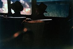 Untitled (two men in hats on train at night) by Saul Leiter