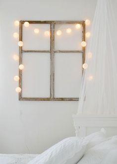 Une décoration murale pour une chambre romantique réalisée avec un cadre de fenêtre en bois de récup et une guirlande électrique avec des boules blanches pour une lumière douce le soir venu.