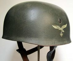 Reproduction WW2 German Paratrooper Helmet M38. Finished in textured green paint where the texture is visible but is worn down to a smooth touch. It has a single Luftwaffe decal which is 100% visible and 99% intact. http://www.warhats.com/store/p472/German_Paratrooper_Helmet_M38_-_Textured_green_finish_-_single_decal.html www.warhats.com