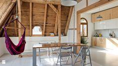 mieszkanie na poddaszu, drewniane stropy, wiszący fotel z fioletowej tkaniny, szara lampa wisząca