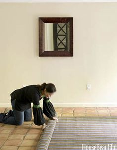 The stripes on an all-weather rug optically draw guests into the house.   - HouseBeautiful.com