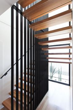 This home features minimalist floating timber stair treads wrapped around a woven steel mesh blade wall.  Courtesy of: Archiblox