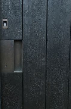 Full gator Shou Sugi ban timber entrance door with bronze recessed handle, bronze biometric entry with digital lock by The Cave architecture and design Detail Architecture, Garage Door Lock, Charred Wood, Timber Cladding, Timber Wood, Bedroom Doors, Entrance Doors, Front Doors, Facades