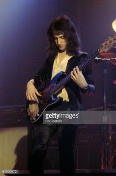 John DEACON  performing on stage in 1977 photo by Fin Costello Getty Images