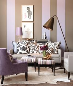 Lilac And Taupe Living Room --  Refined furniture and a complementary palette tames an audacious combination of patterns.  In this living room design, oversized, painted stripes visually raise the ceiling without looking busy. The large, playful floor lamp lends a fresh, fun perspective. A lively range of purple and brown hues, combined with a mixture of striped and floral patterns, also adds a lighthearted note.      * Designer: Stacey Smithers
