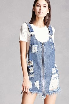 A denim overall mini dress featuring a destroyed design with frayed trim, full-length zipper front, adjustable shoulder straps, distressed chest patch pocket, and two back patch pockets.
