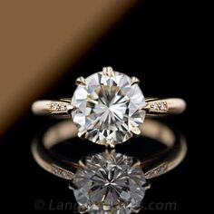 A 3.00 + carat round brilliant cut diamond shines in this vintage style 14 karat rose gold solitaire. The diamond is set with eight elegant pointed prongs and enhanced by three round brilliant cut diamonds set on either side along the tapered band. Sweet simplicity.