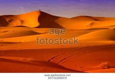 Two people admire the sunset placed on a hill at Erg Chebbi spot