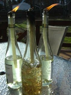 Citronella wine bottle candles! Love this! Wine bottle or whisky bottle, tiki torch feul, thick wick, washer to keep wick from falling, and decorative stones in bottle   That easy!