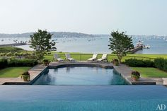 An infinity-edge pool with bluestone coping overlooks Oyster Bay Cove.