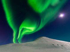 Bailando con la luna, Islandia. Los haces de luz vivas son el resultado de colisiones entre partículas cargadas liberadas por la atmósfera y  partículas gaseosas del sol en la atmósfera de la Tierra. Este tiro fue capturado por Andrew George.National-Geographic