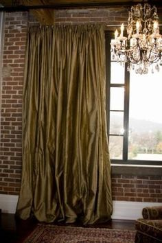 silk curtains, brick wall, chandelier.