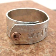 """Writing is Re-Writing"" aluminum ring with copper rivet. This is a cool, unique gift for the author in your life. The work has just begun once you write ""The End""."
