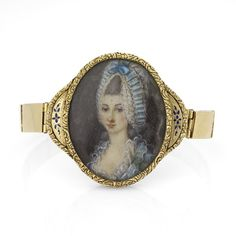 An 18K Georgian bracelet comprised of a central oval plaque featuring a painted portrait of a woman in blue, in a gold and blue enamel frame, with a thin link bracelet. Circa 1800.