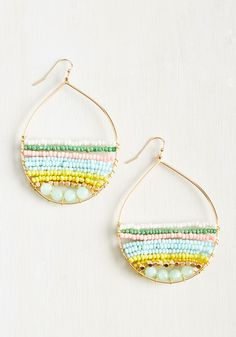 Give your style a funky-fresh upgrade with the addition of these golden hoop earrings! Adorned with strands of pastel beads in white, kelly green, rose, aqua, and marigold hues, this groovy pair assures your accessory game is going strong!