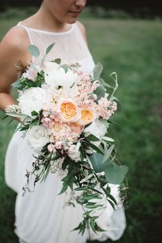 Rachel's cascading bouquet photographed by Michelle Lyerly at Sawyer Family Farm in Cashiers, NC. Juliet garden roses, stock, eucalyptus, olive leaf, tuberose, roses, spray roses and more.