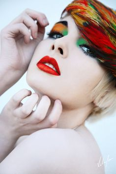 Rainbow makeup red lips orange and green eyeshadow white pale face red and green feathers