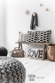 Drevená lavica s vankúčmi a jednoduché vešiaky v predsieni