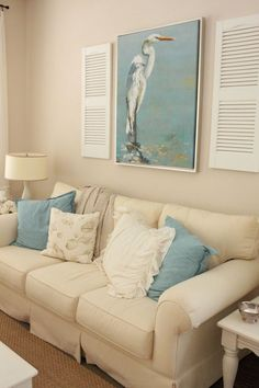 Coastal-themed living room with shutters on either side of artwork