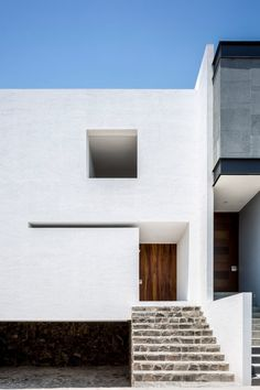 Abraham Cota Paredes' inward-looking Cave House features huge window to tree-planted atrium