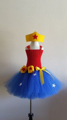 Super Woman Inspired Tutu Dress with Crown and Wristband Cuffs This beautiful Super Woman Inspired Tutu Dress will bring out the superhero of your little one. The tutu is made with blue tulle with sta