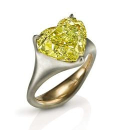 Sotheby's: Centering a fancy yellow, heart-shaped diamond weighing 6.10 carats.  Mounted in brushed 18k white gold and 18k yellow gold.