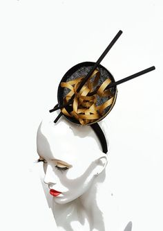 A fun foodie fascinator - emulating a bowl of noodles complete with chopsticks. I have blocked black sinamay into a bowl shape, this has a wired edge and gold trim. The noodles are stiffened gold ribbon, topped with a pair of black chopsticks. All mounted onto a black satin covered headband for ease of wearing. Designed to be worn to the right side of the head. Made in the UK and ready to ship