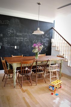 I'm drawn to this room...maybe the simplicity, rustic table and mis-matched chairs (always a love of mine), the chalkboard wall, the wildflowers naturally making a statement, or maybe just because I'm so used to seeing toys in my dining room too! :) Its sheer inspiration to me.