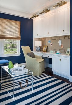 Gorgeous navy workspace, love the pinboard, cabinetry  and lucite table.