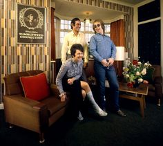 """The former Reggie Dwight, later known as Elton John, laughs with his mom Sheila Fairebrother and her husband Fred (whom he affectionately called """"Derf,"""" Fred spelled backwards) in their suburban London apartment in 1970. At this point John was just three albums into his prolific career, and still had countless hits — """"Rocket Man,"""" """"Daniel,"""" """"Bennie and the Jets,"""" """"Candle in the Wind"""" among them — in his future. """"When he was four years old,"""" the future Elton John's mother said of her prodigio..."""